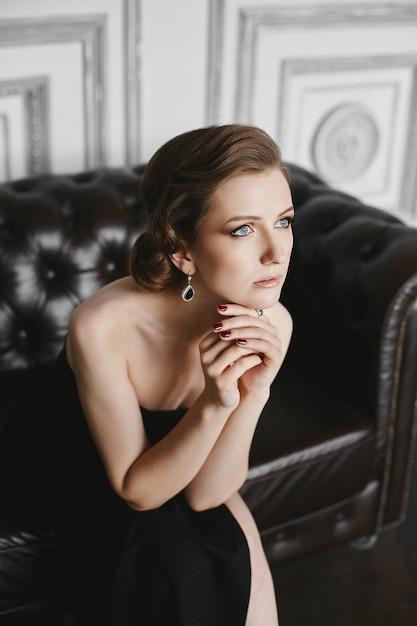 깊고 푸른 눈, 저녁 메이크업 및 헤어 스타일을 가진 아름다운 모델 여자, 실내 빈티지 소파에 포즈 검은 드레스를 입고 프리미엄 사진