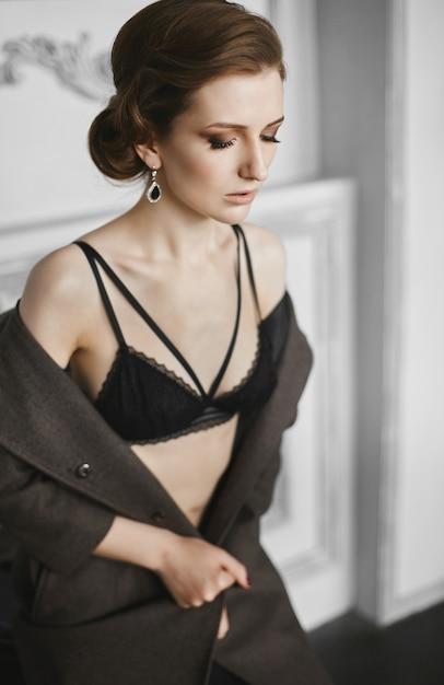 트렌디 한 헤어 스타일과 검은 색 란제리의 저녁 화장과 실내에서 포즈를 취하는 속박 코트와 아름다운 모델 여자 프리미엄 사진