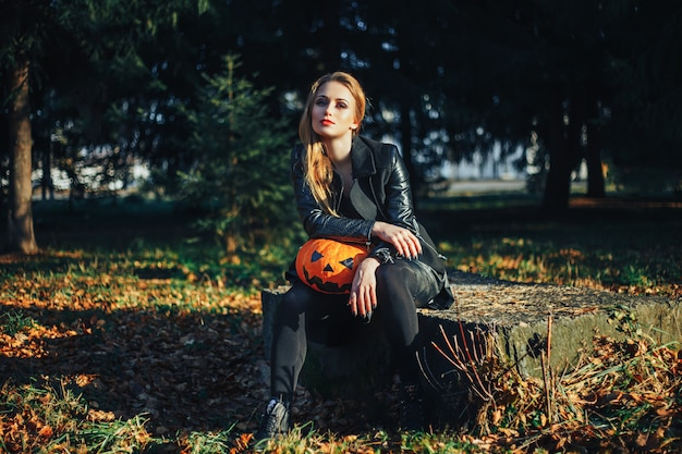 Beautiful modern witch holding halloween pumpkin in the forest Premium Photo