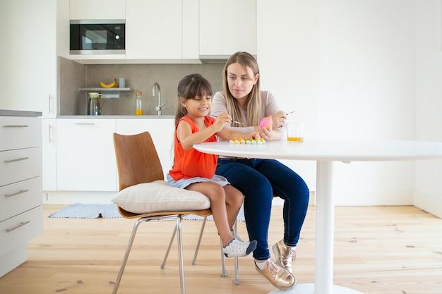 キッチンで娘と一緒に美しいお母さん絵画イースターエッグ。 無料写真