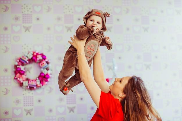 美しいお母さんが彼女の素敵な息子を空中に投げつける 無料写真