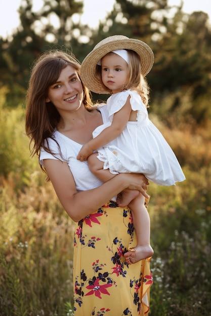 Красивая мама и дочь на прогулке в поле Premium Фотографии