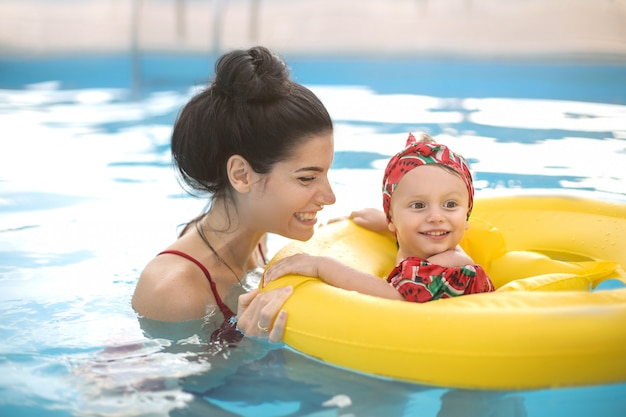 Красивая мама и дочь, плавание в бассейне Premium Фотографии