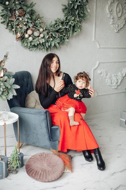 Красивая мама и ее милая маленькая дочь сидят в кресле под рождественским венком Бесплатные Фотографии