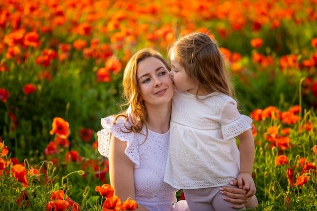 春のケシの花畑、チェコ共和国で美しい母と娘 Premium写真