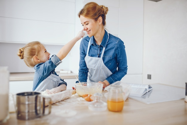 Beautiful mother in a blue shirt and apron is preparing dinner at home in the kitchen Free Photo