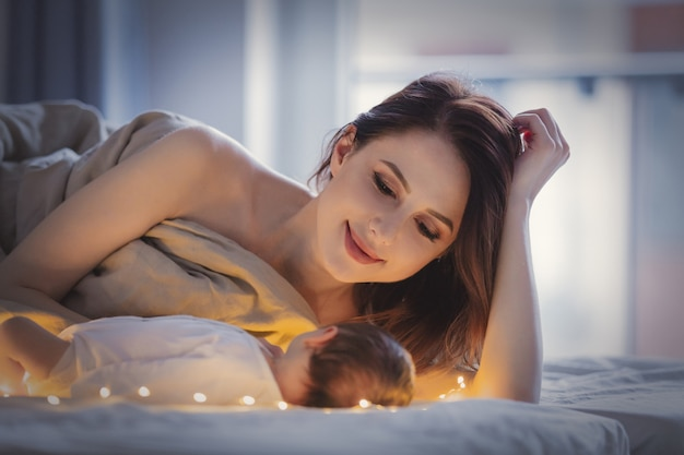 Beautiful mother and child in a bed in morning time. Premium Photo