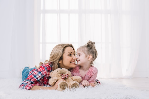 Beautiful mother and daughter lying on fur making funny face with teddy bear Free Photo