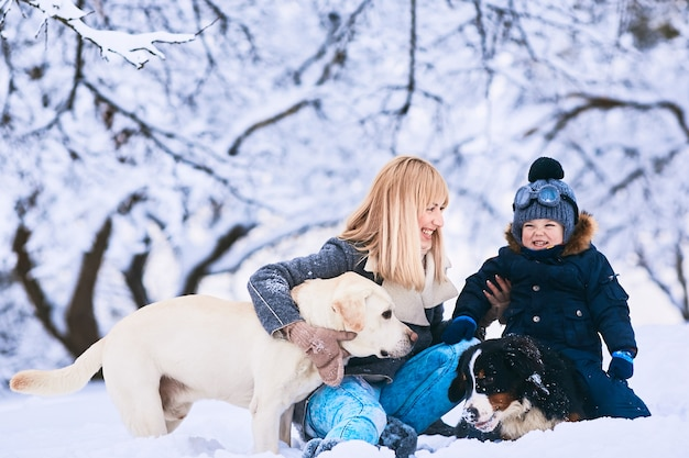 The beautiful mother, son and dogs sitting on the snow Free Photo