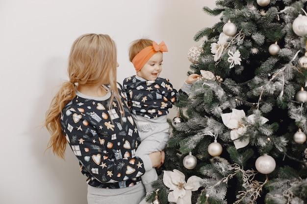 Красивая мать с ребенком. семья в рождественской атмосфере. люди носят елку. Бесплатные Фотографии