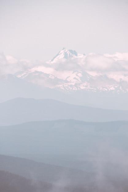 雪に覆われ、霧深い天候の間に雲に囲まれた美しい山 無料写真