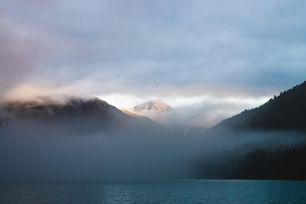 Красивое горное озеро среди огромных гор и леса в тумане в золотой час. солнце раскрашивает плотные низкие облака. большой камень блестит на восходе солнца. красочный альпийский расслабляющий пейзаж с туманом в пастельных тонах. Premium Фотографии