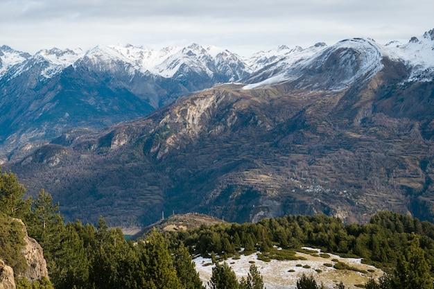 Bellissima catena montuosa ricoperta di neve avvolta nella nebbia, ideale per uno sfondo naturale Foto Gratuite