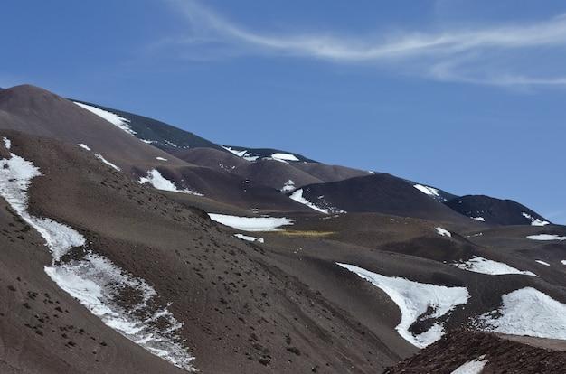 明るい空の下で部分的に雪に覆われた美しい山岳風景 無料写真