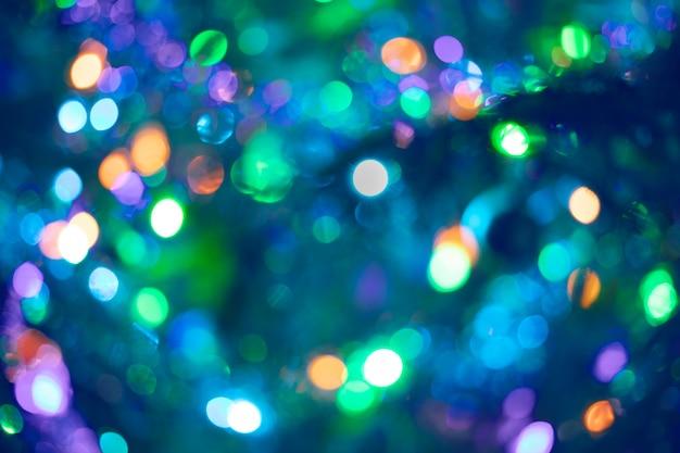 Красивое разноцветное боке в пурпурно-сине-зеленом цвете в качестве фона или обоев. рождество или новый год расфокусированным фон боке. Premium Фотографии