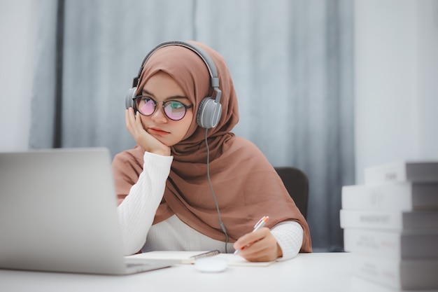 Beautiful muslim student girl using a laptop computer learning online at home. distance learning online education. Premium Photo