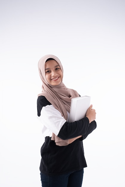 The beautiful muslim woman hugging book in her arms Premium Photo
