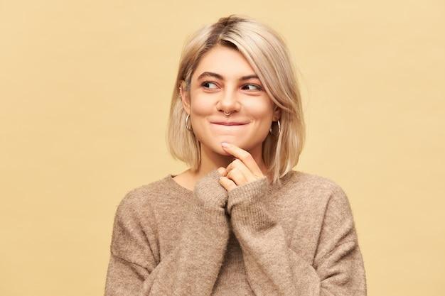 Красивая загадочная европейская девушка в стильном уютном свитере, поразившая загадочным выражением лица, глядя в сторону и улыбаясь, придумывая идею, думая о плане, изолированном у глухой стены Бесплатные Фотографии