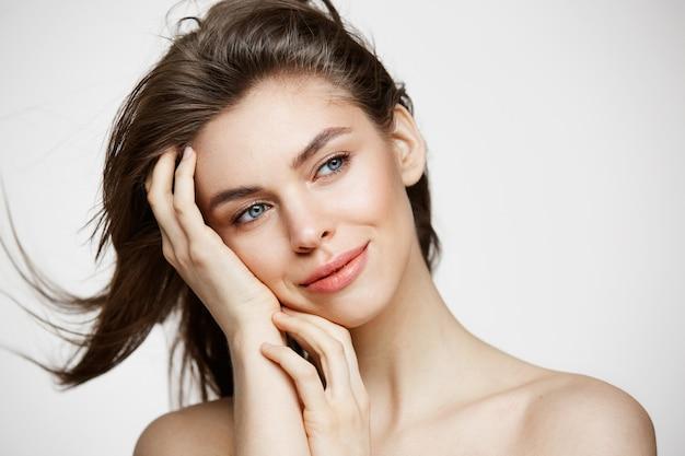 흰 벽에 머리를 만지고 웃 고 완벽 한 깨끗 한 피부와 아름 다운 벌 거 벗은 젊은 여자. 페이셜 트리트먼트. 무료 사진