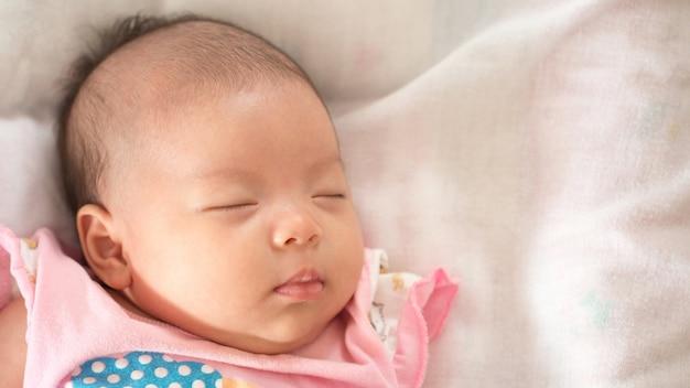 Beautiful newborn asian baby girl sleeping in her bed photo