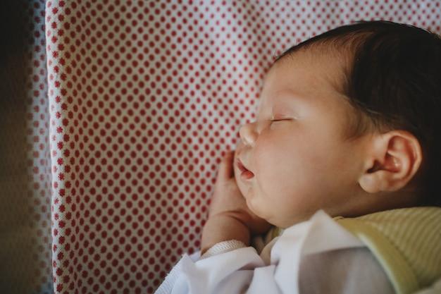 Beautiful newborn child lies on a bed and sleeps Free Photo