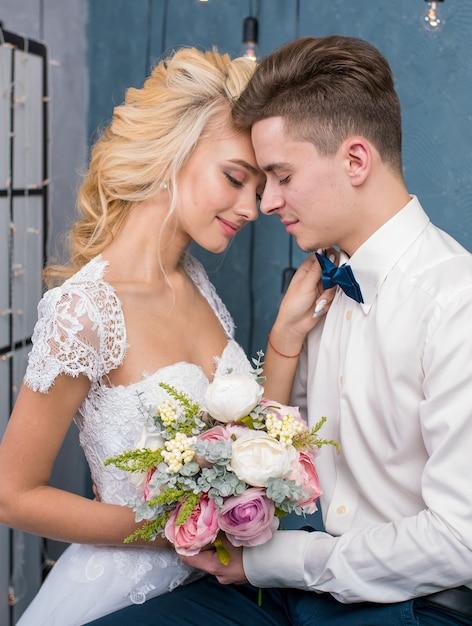 Красивые молодожены сидят и держатся за руки в серой студии. портрет жениха и невесты в кружевном платье. нежный свадебный портрет. Premium Фотографии