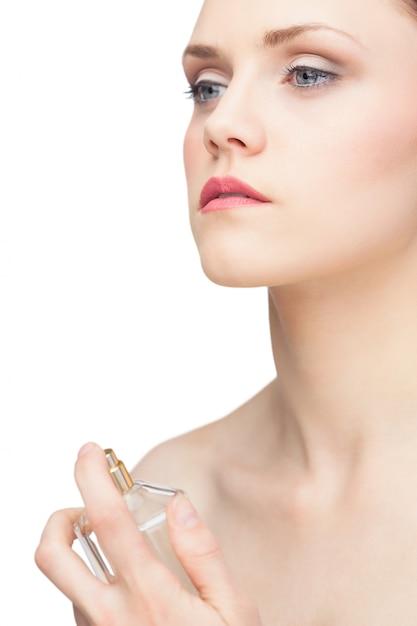 Beautiful nude model spraying perfume Premium Photo