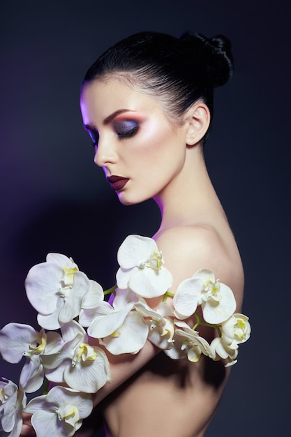 Beautiful nude woman with a branch of white orchid Premium Photo