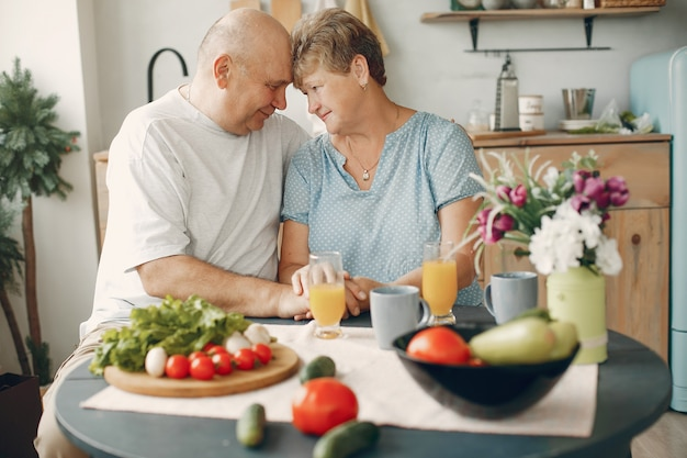 Beautiful old couple prepare food in a kitchen Free Photo