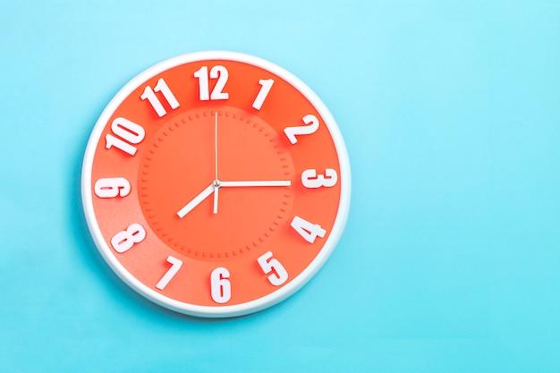 Beautiful orange wall clock on blue background Premium Photo