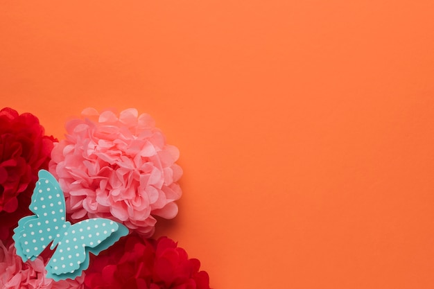 Beautiful origami paper flowers and polka dotted blue butterfly on orange backdrop Free Photo