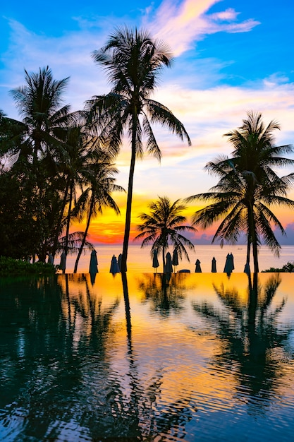 Beautiful outdoor nature landscape with sea ocean and coconut palm tree around swimming pool at sunrsie or sunset Free Photo
