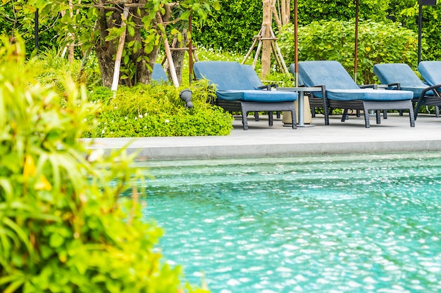 Beautiful outdoor swimming pool in hotel and resort with chair and deck for leisure vacation Free Photo