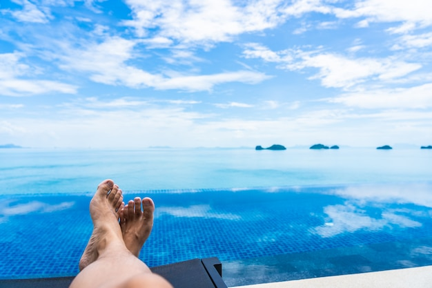 Beautiful outdoor swimming pool with sea ocean on white cloud blue sky Free Photo