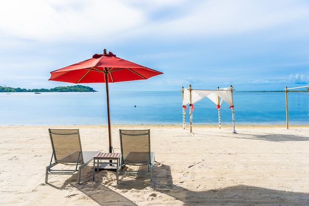 Beautiful outdoor tropical beach sea ocean with umbrella chair and lounge deck around there on white cloud blue sky Free Photo