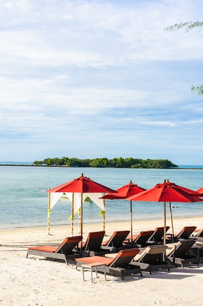 Beautiful outdoor tropical beach sea ocean with umbrella chair and lounge deck Free Photo