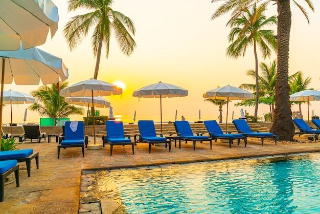 Красивая пальма с бассейном с зонтиком в роскошном курортном отеле Premium Фотографии
