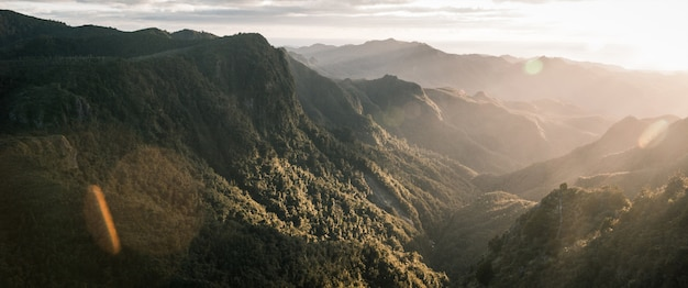 Beautiful panoramic shot of mountains and rocky cliffs and natural fog Free Photo