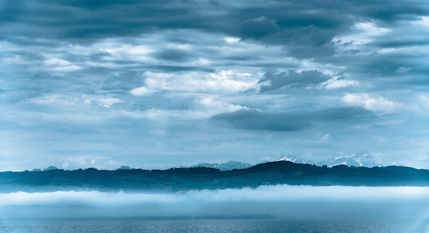 Beautiful panoramic shot of a sea with hills on the background under a cloudy sky Free Photo
