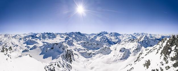 Bella ripresa panoramica delle catene montuose innevate sotto un cielo soleggiato blu chiaro Foto Gratuite