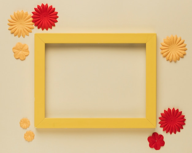 Beautiful paper flower cutout and wooden frame border on beige background Free Photo