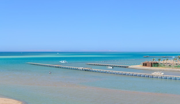 Beautiful paradise beach of the blue sea with a pier and a yacht panorama Premium Photo