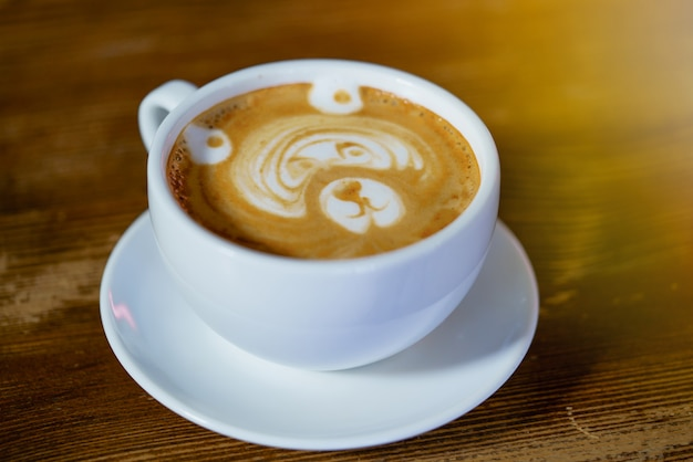 Beautiful pattern in the form of bear in a white cup with a latte maded in the restaurant. Premium Photo