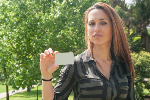 Beautiful pensive young woman holding business card Free Photo