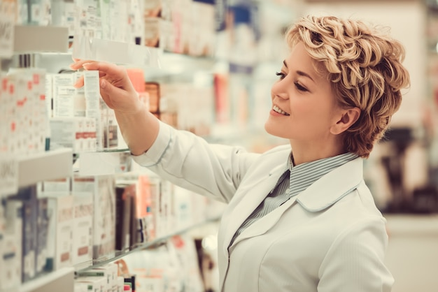 Beautiful pharmacist is searching for medicine. Premium Photo