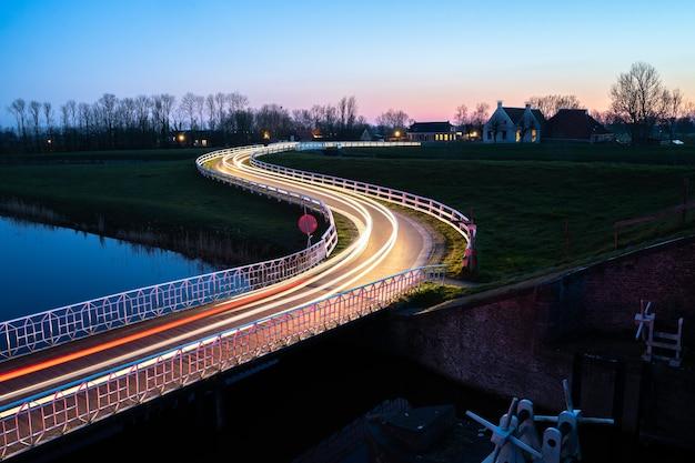 夜の川の横に車のライトトレイルがある通りの美しい写真 無料写真