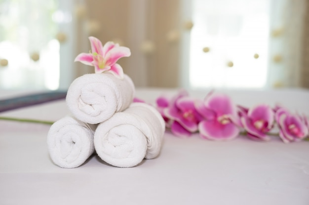beautiful pink orchid on white towel in spa salon. Free Photo