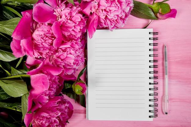Beautiful pink peony flowers with notebook Premium Photo