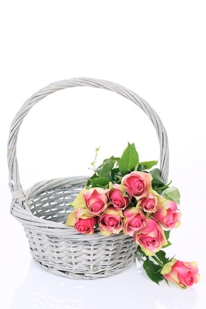 白い背景の上のバスケットの美しいピンクのバラ 無料写真
