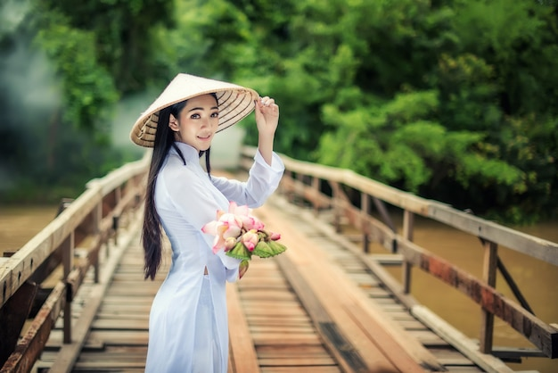 Beautiful portrait of asian girls with ao dai walk the bridge with lotus, vietnam traditional dress costume woman at vietnam. Premium Photo
